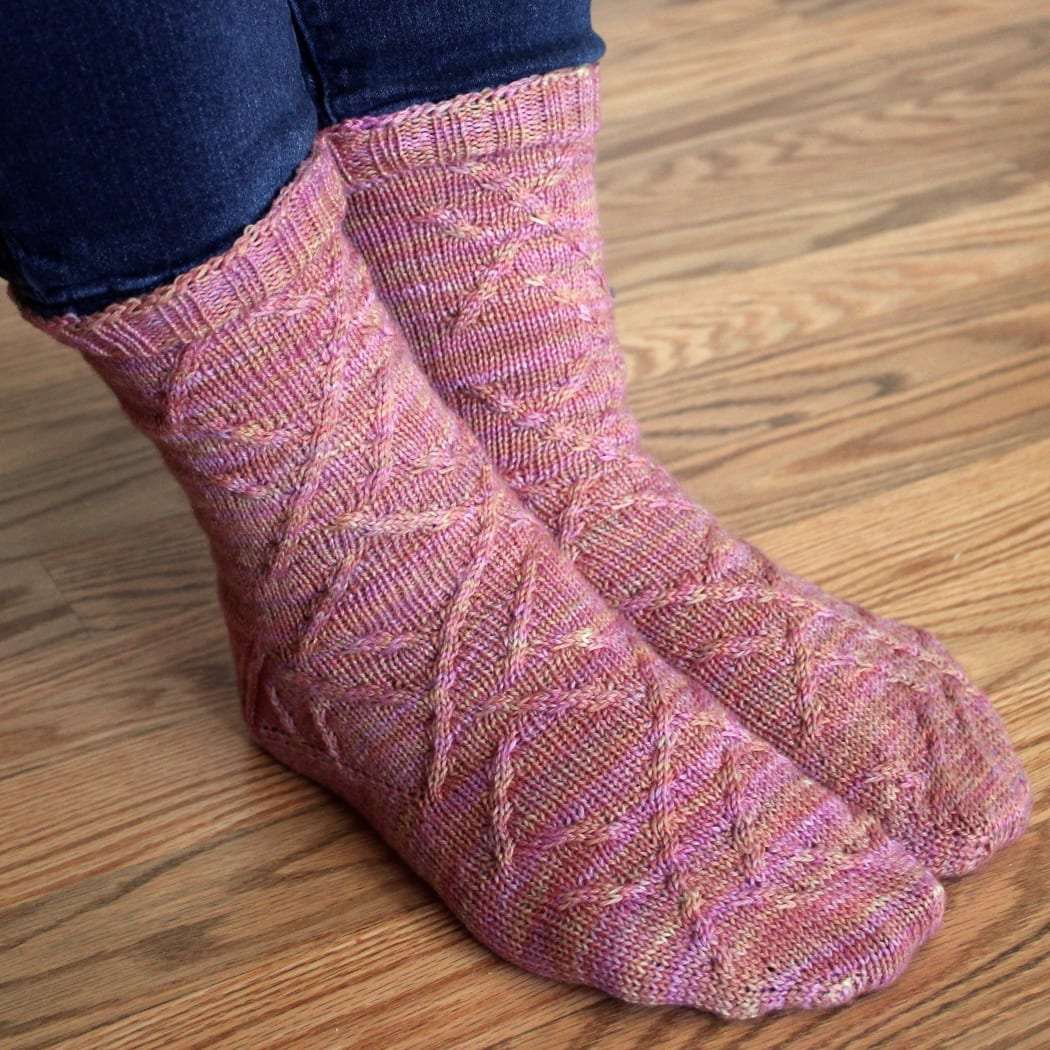 Crossed feet wearing pink-orange socks with cabled surface detail.