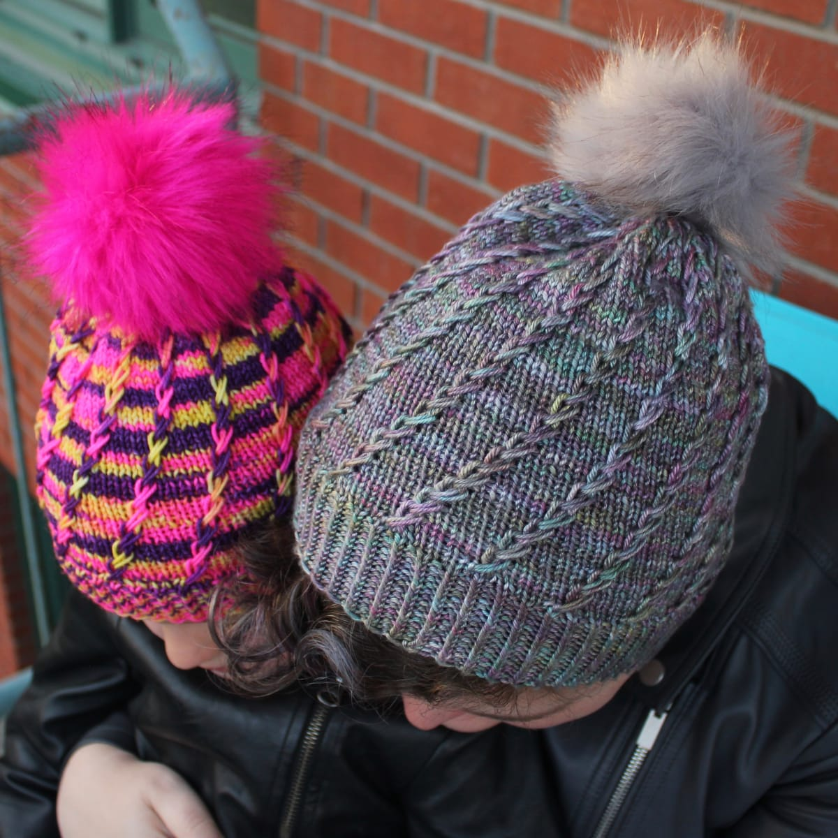 Top-down view of woman and child wearing toques with spiralling criss-crossing surface textures and coordinating pompoms.