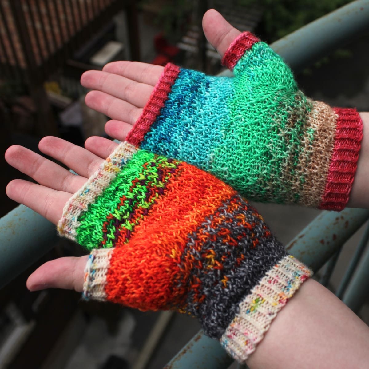 Palm-up view of mismatched multicoloured fingerless mitts with slipped-stitch texture.