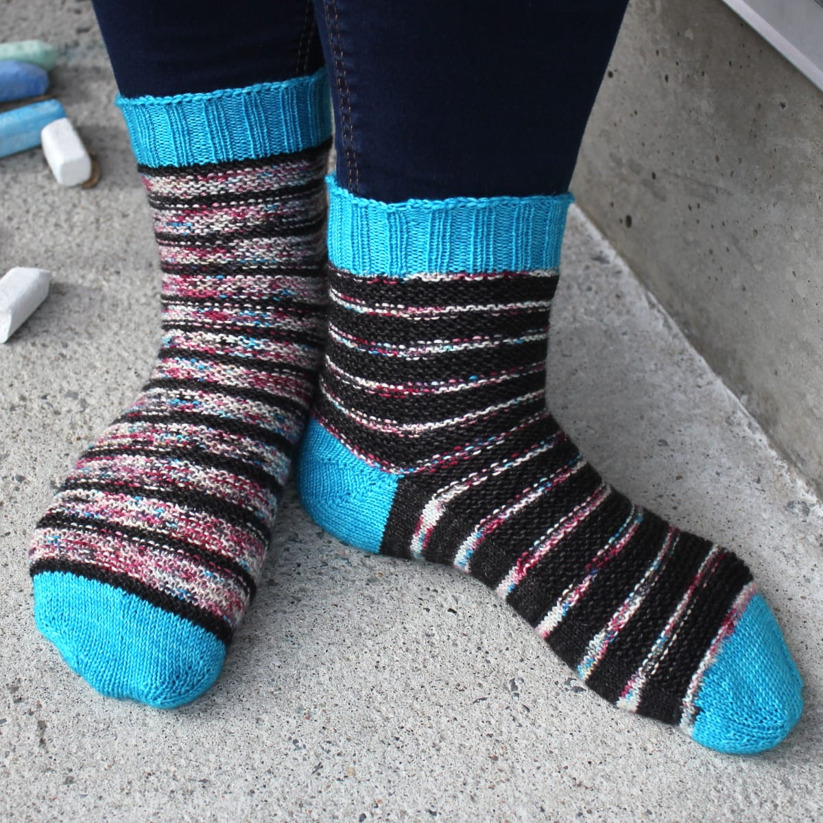 Front and side view of black and subtly-multicoloured striped socks with bumpy surface texture and bright blue heels, toes, and cuffs.