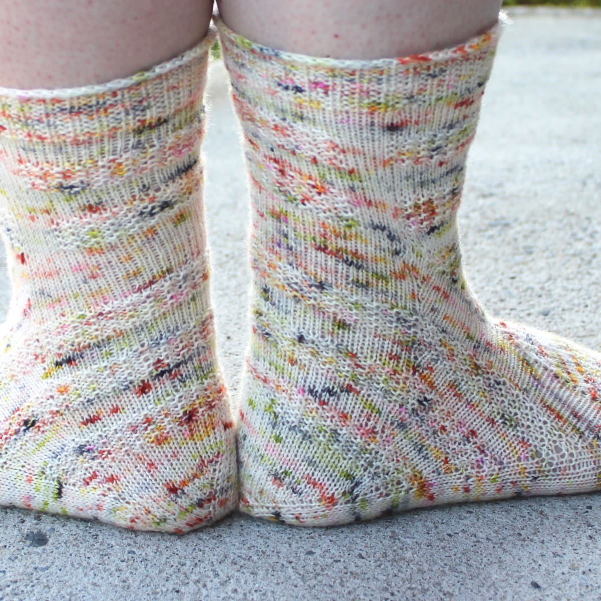 Back view of heavily-speckled white socks with semicircular texture details.