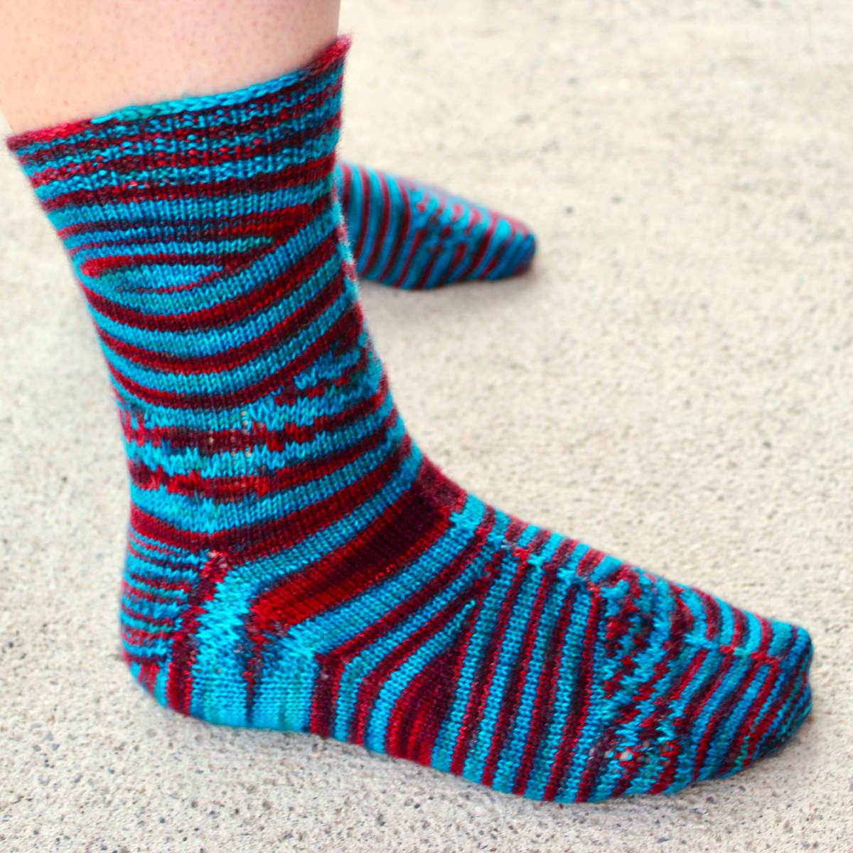 Side view of blue and red socks with shifting and pooling colour patterns and subtle surface texture.