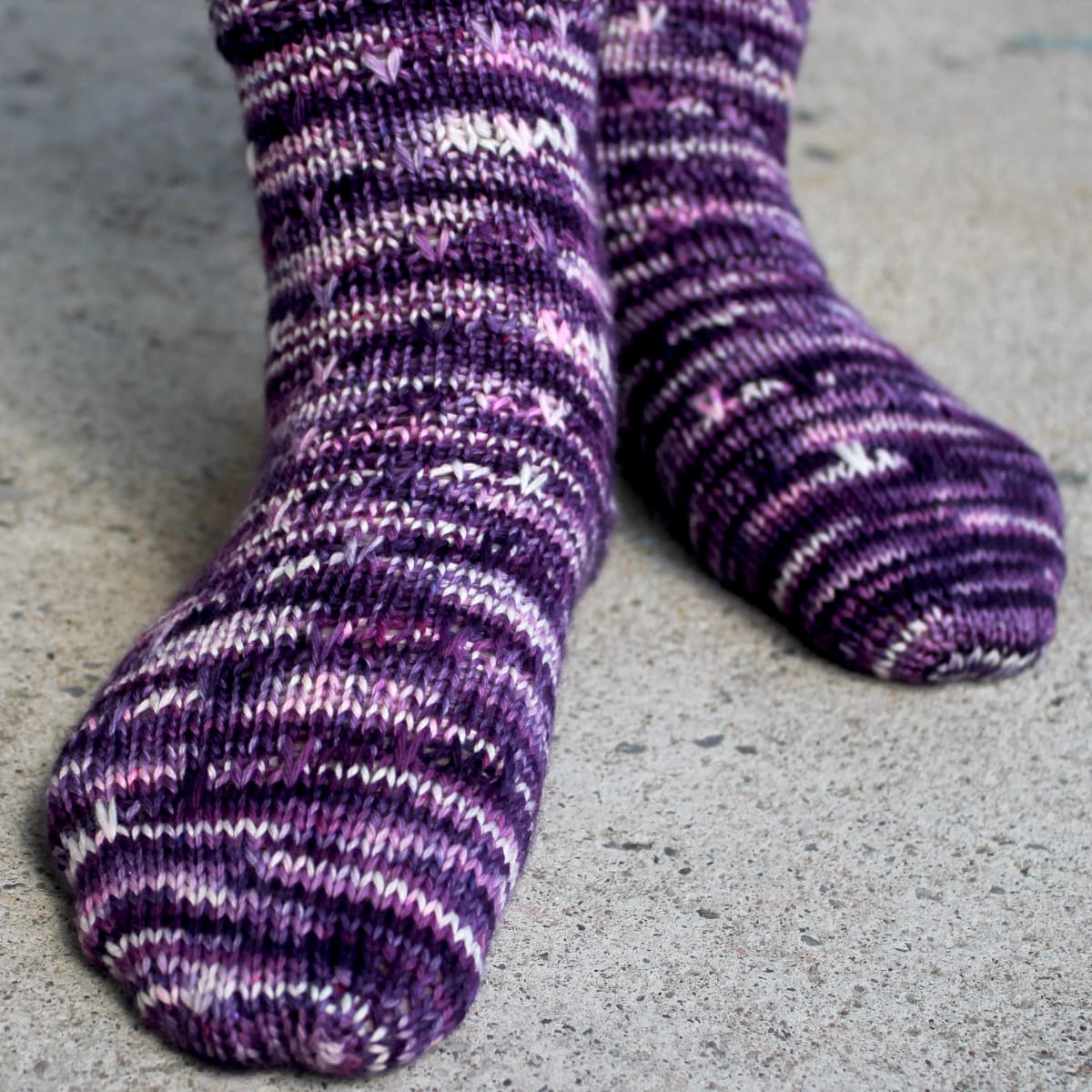 Feet wearing dark purple, pink, and white socks with slipped-stitch texture.