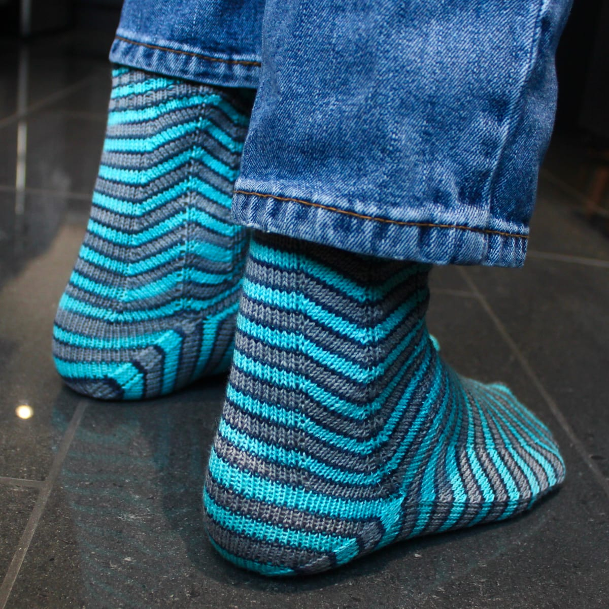 Right-side view of grey and blue socks with stripes that are distorted on the sides.