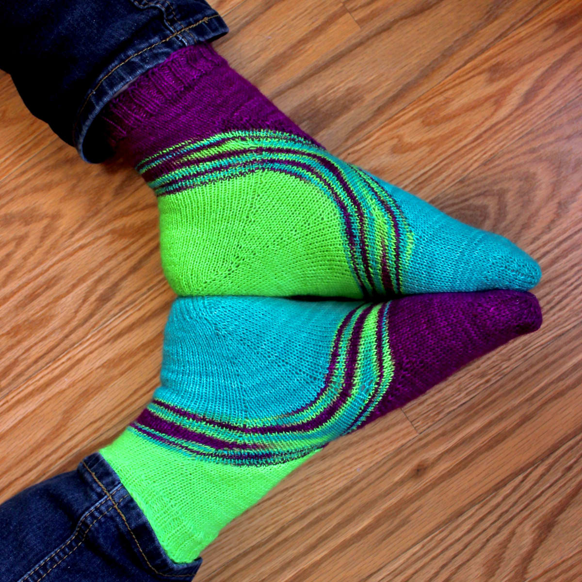 Feet lying sole-to-sole wearing bright green, blue, and purple socks with a multicoloured stripe between the colours.