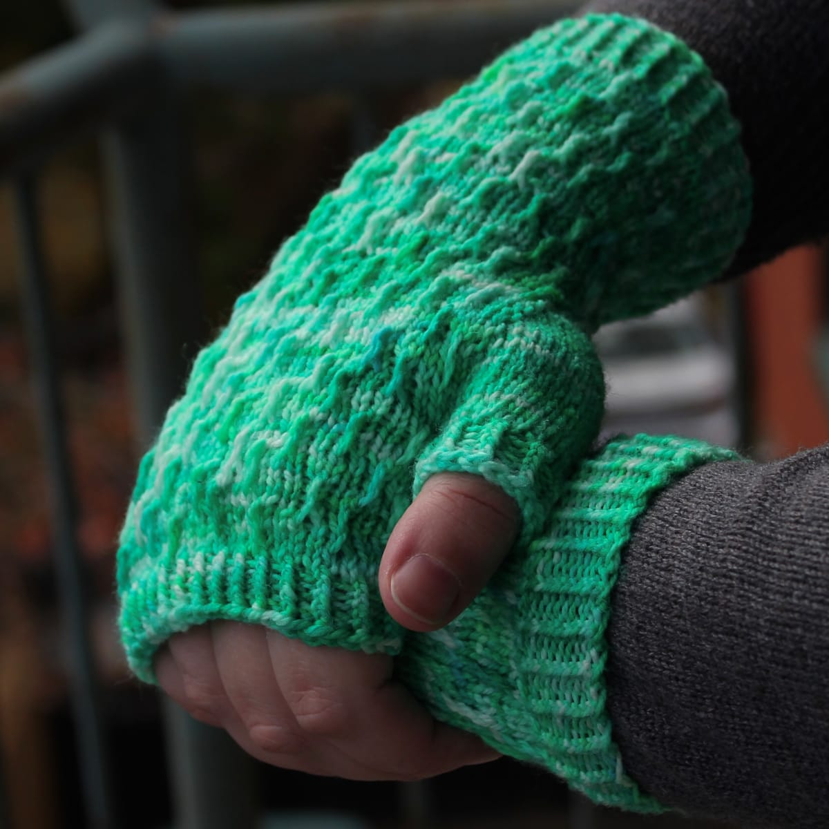Side view of hands draped over each other wearing bright green fingerless mitts with twisted surface detail.