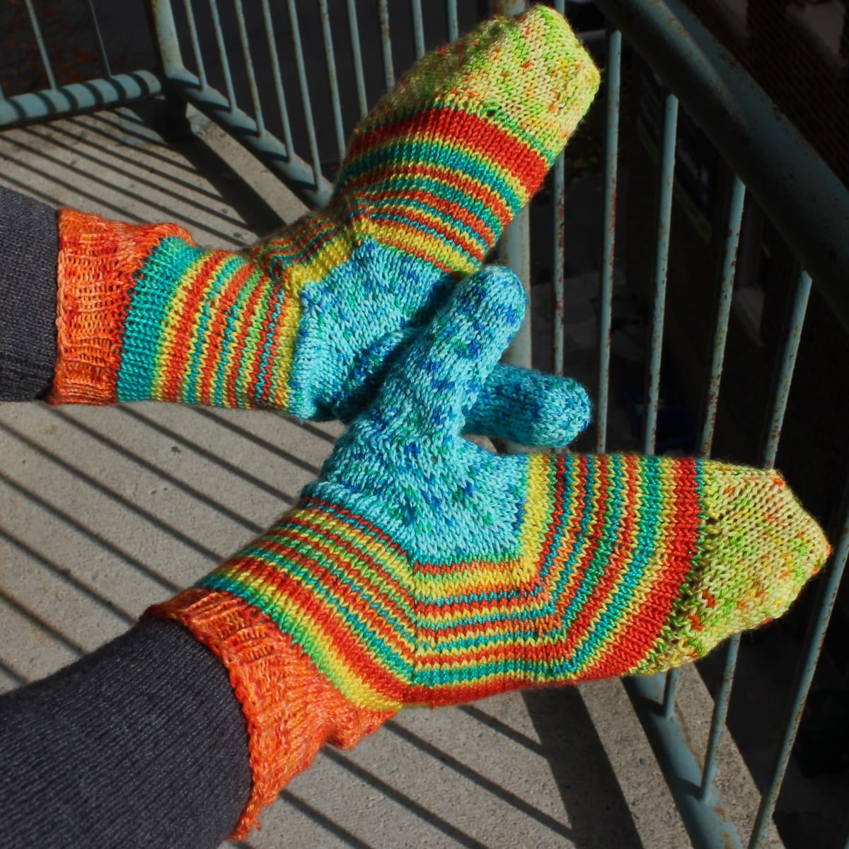 Top-down view of backs of hands wearing bright yellow, blue, and orange mittens with a multicoloured stripe across the palm between the colours.