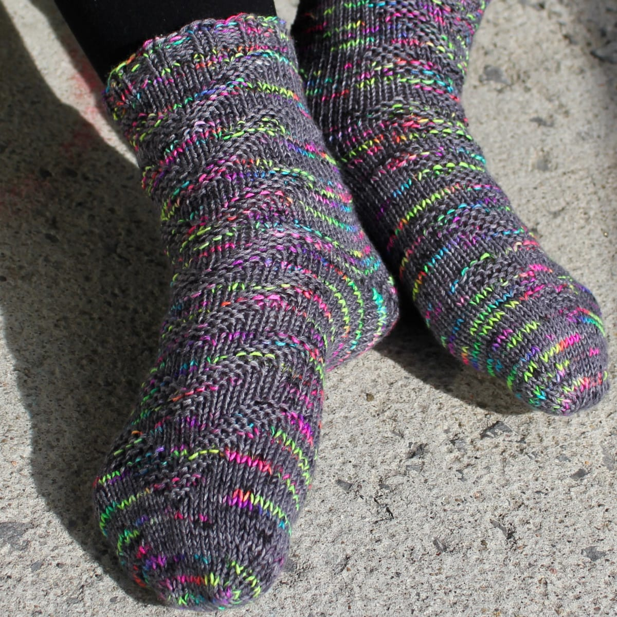 Feet wearing dark grey and rainbow socks with raised chevron texture.