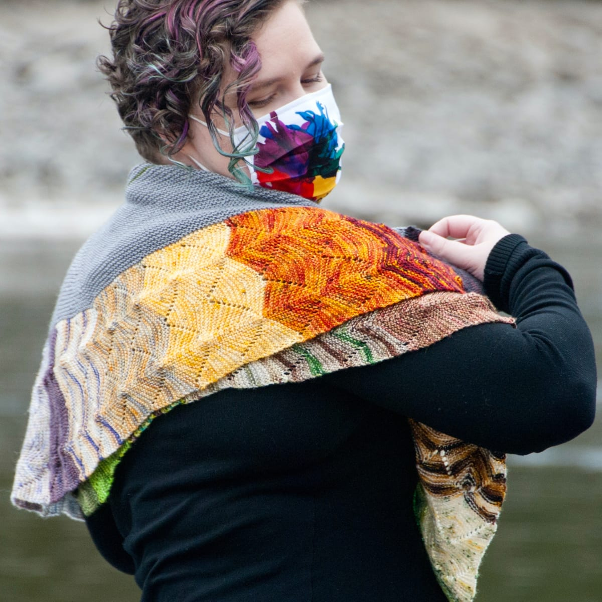 Woman in a mask wearing a large, colourful crescent-shaped knitted shawl with undulating textured lines.