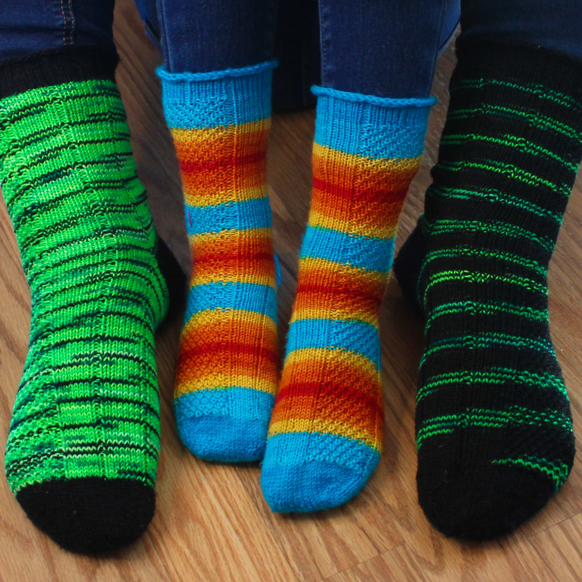 Small child feet wearing striped socks with texture detail between adult feet wearing green and black socks with the same texture detail.