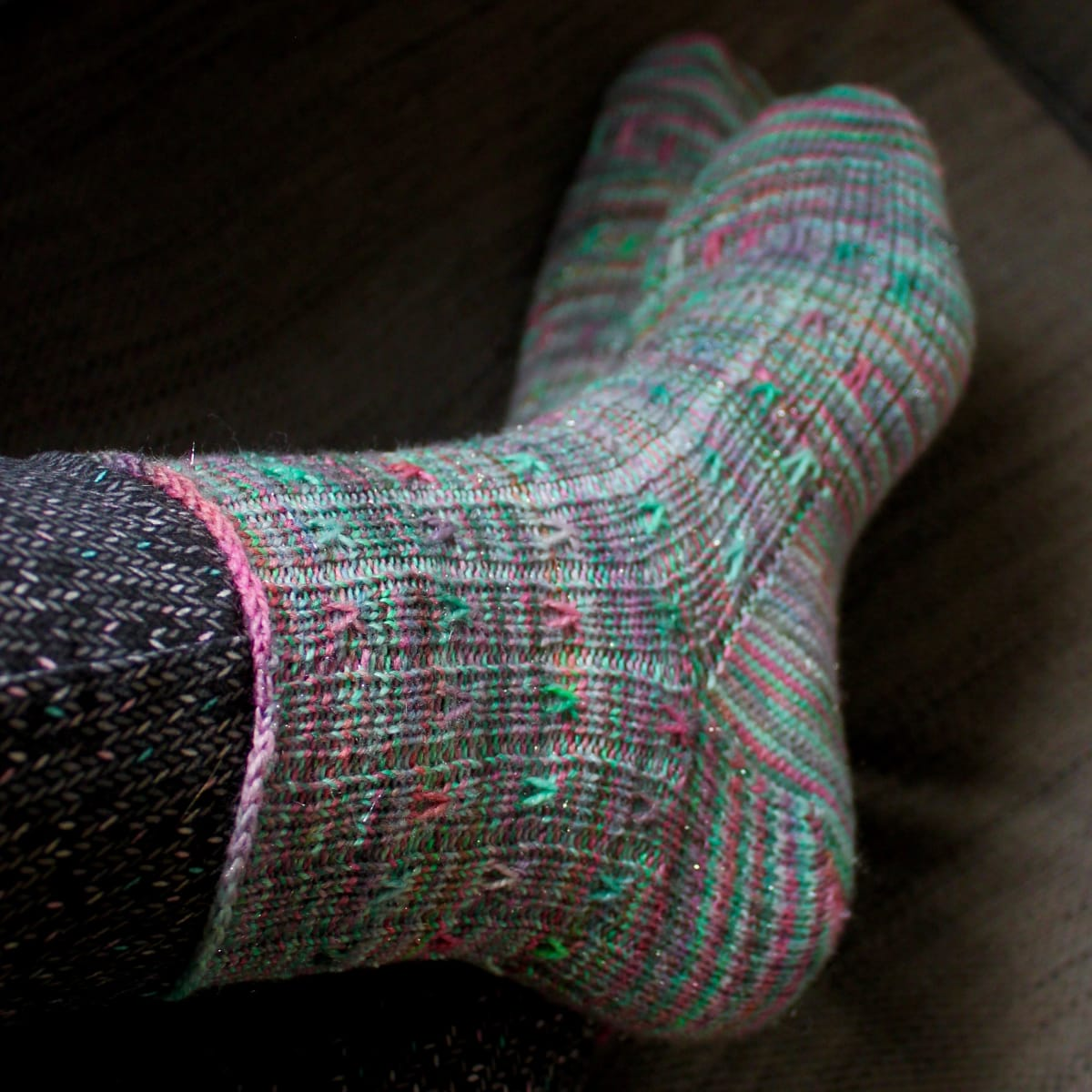 Crossed feet wearing green ribbed socks with coral and purple spiralling surface detail.