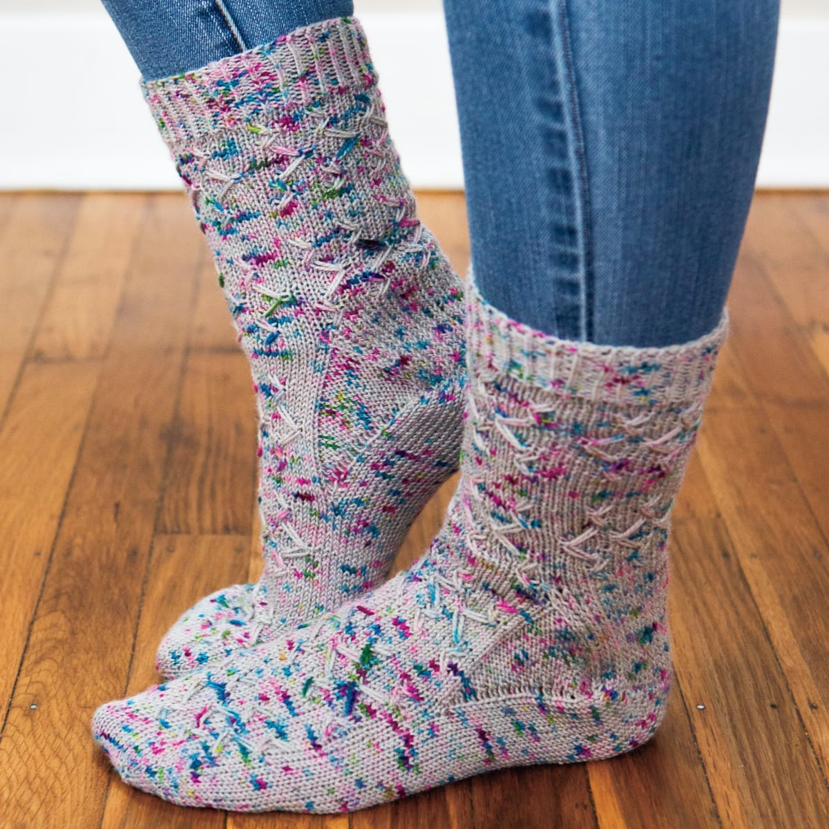 One foot flat and one on tiptoe wearing grey knitted socks with blue and purple speckles and an angular slipped-stitch surface texture.