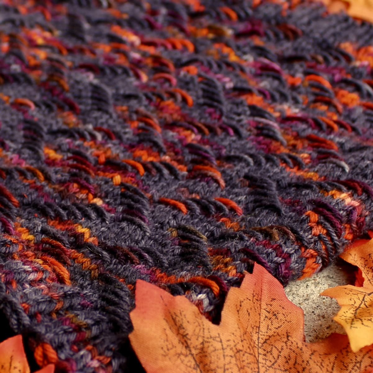 Close up of knitted cowl that is black with bright orange and burgundy highlights in a zigzag texture.