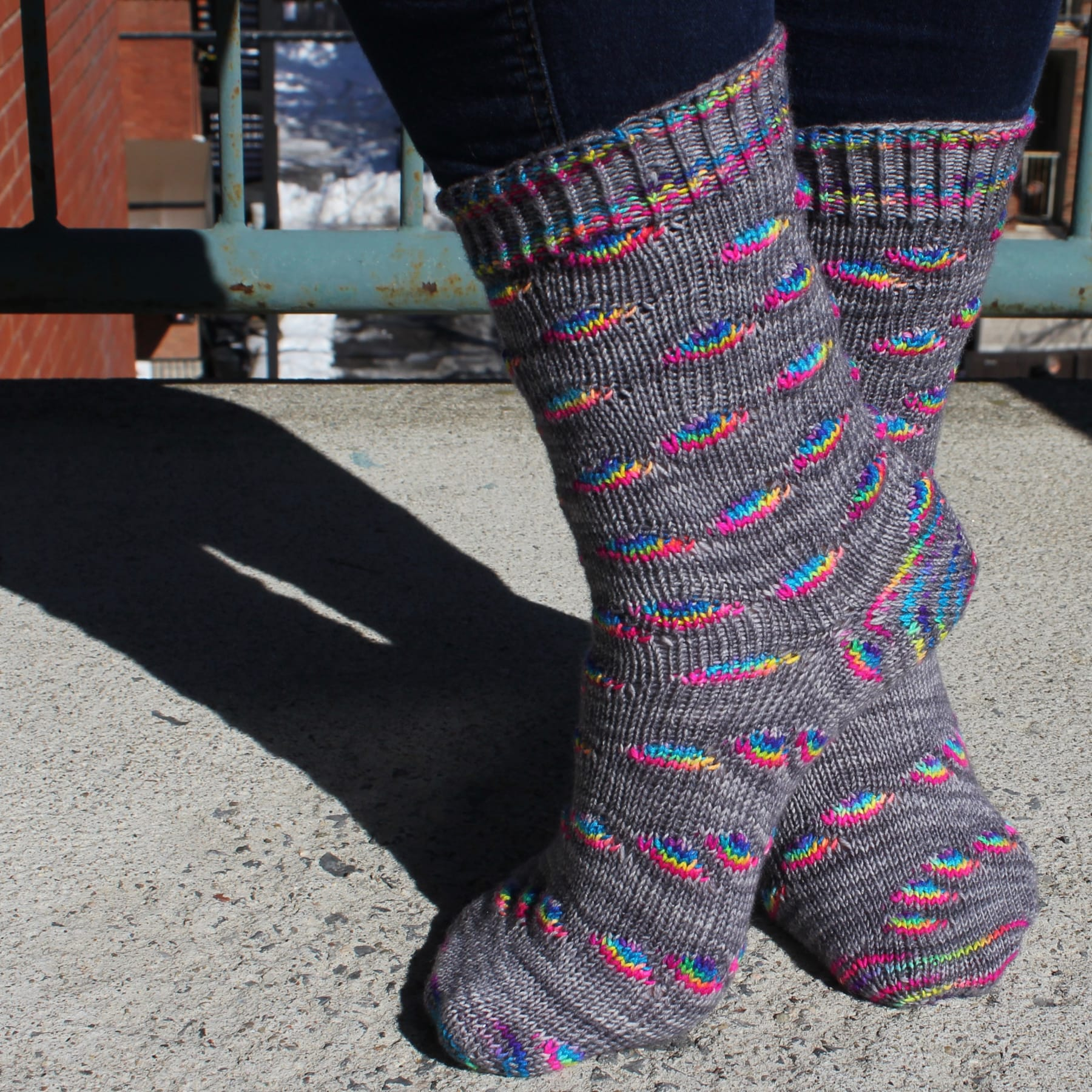 Side view of grey socks with rainbow oval sections and textured cuffs and heels.