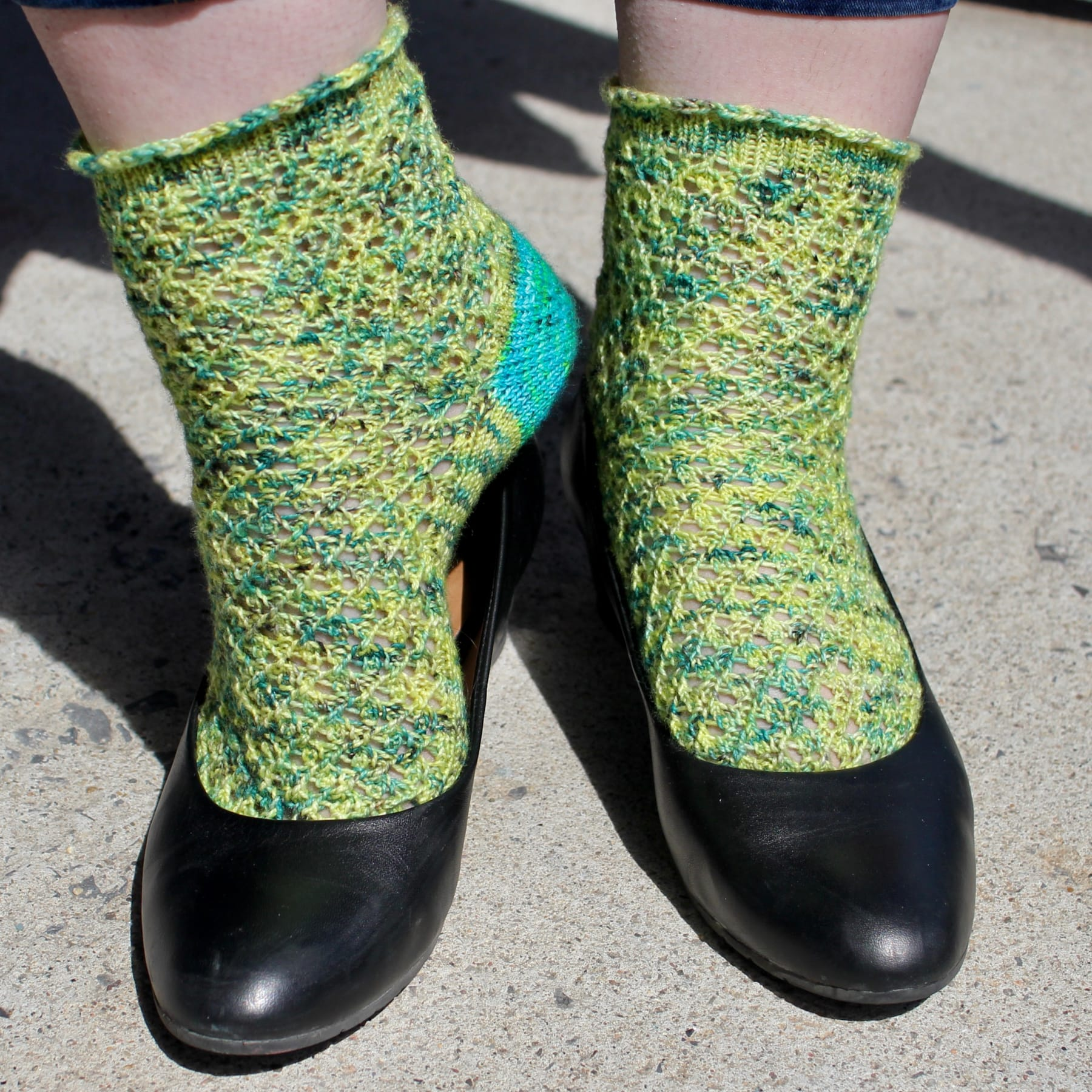 Feet wearing yellow and green lace socks; one foot is turned sideways to reveal a bright blue sock heel.