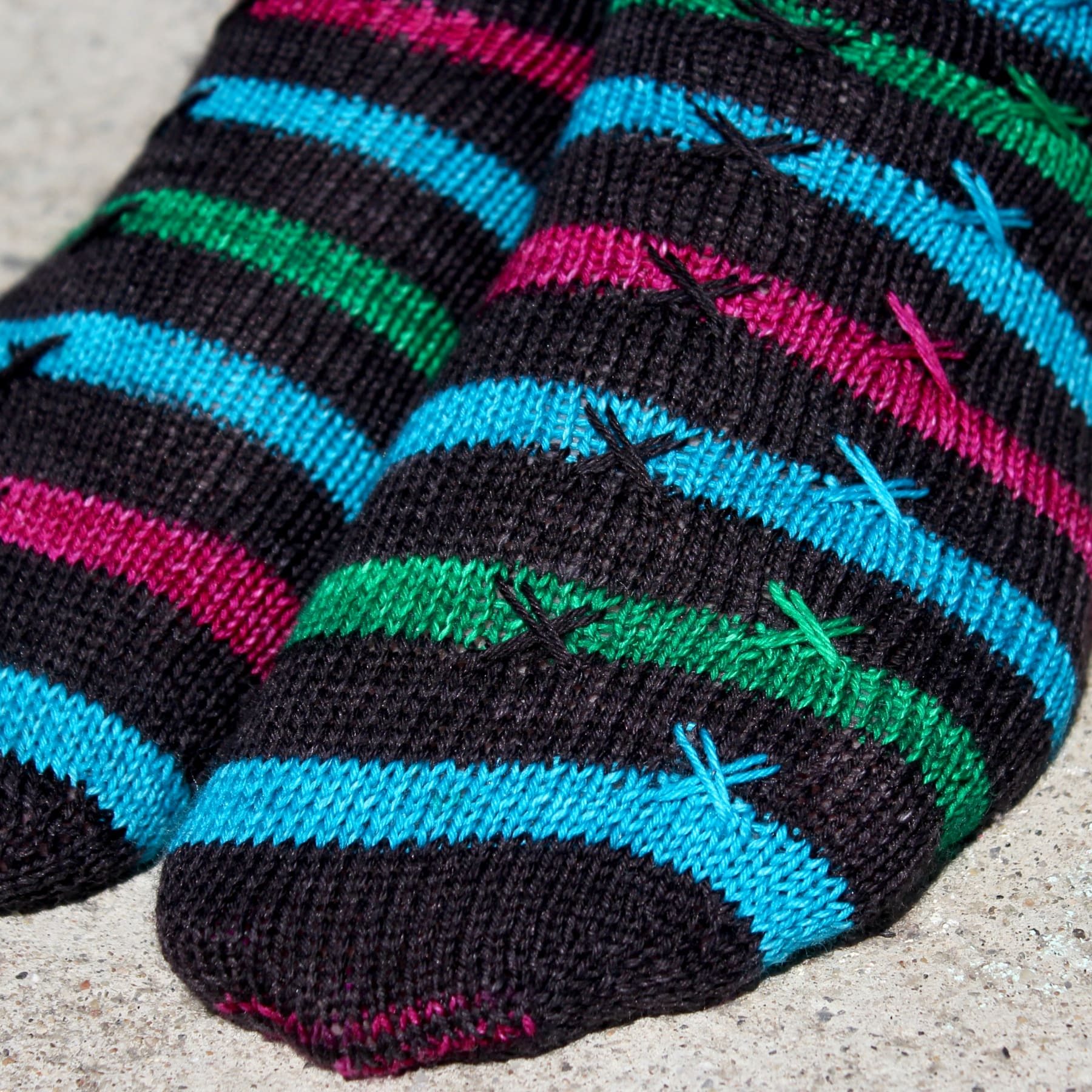 Close up of striped knitted socks with X stitch details on top of the stripes.