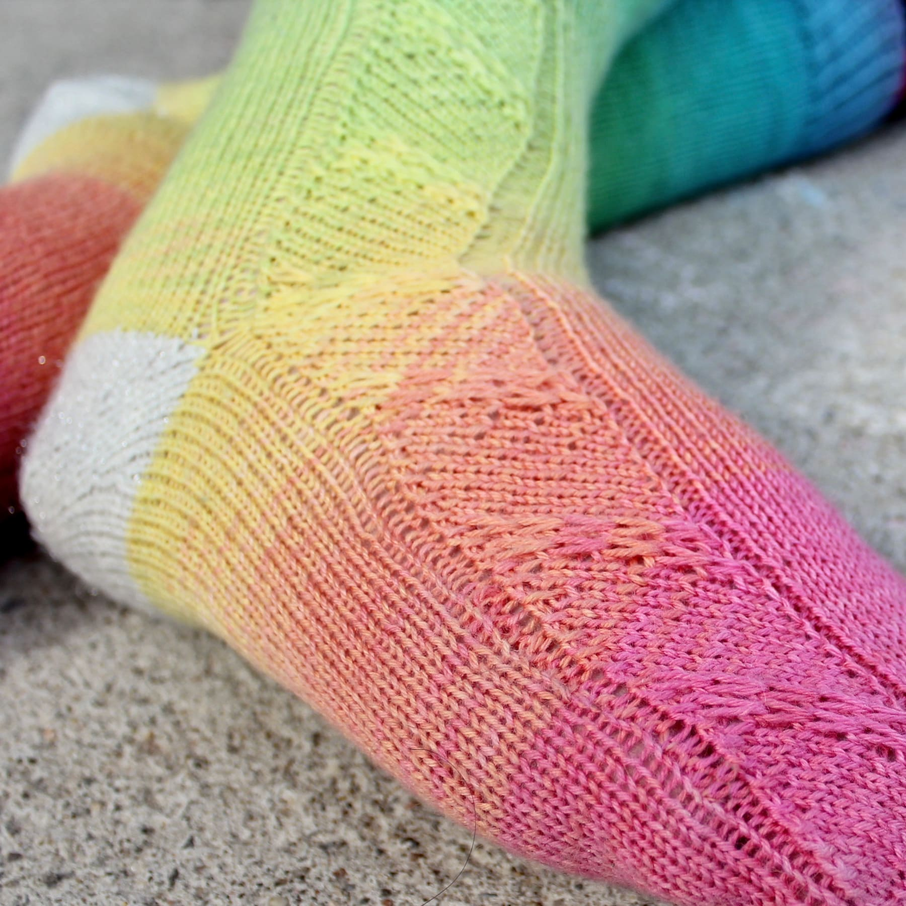Closeup of feet wearing rainbow socks with diagonal slipped-stitch panel and sparkly white heels.