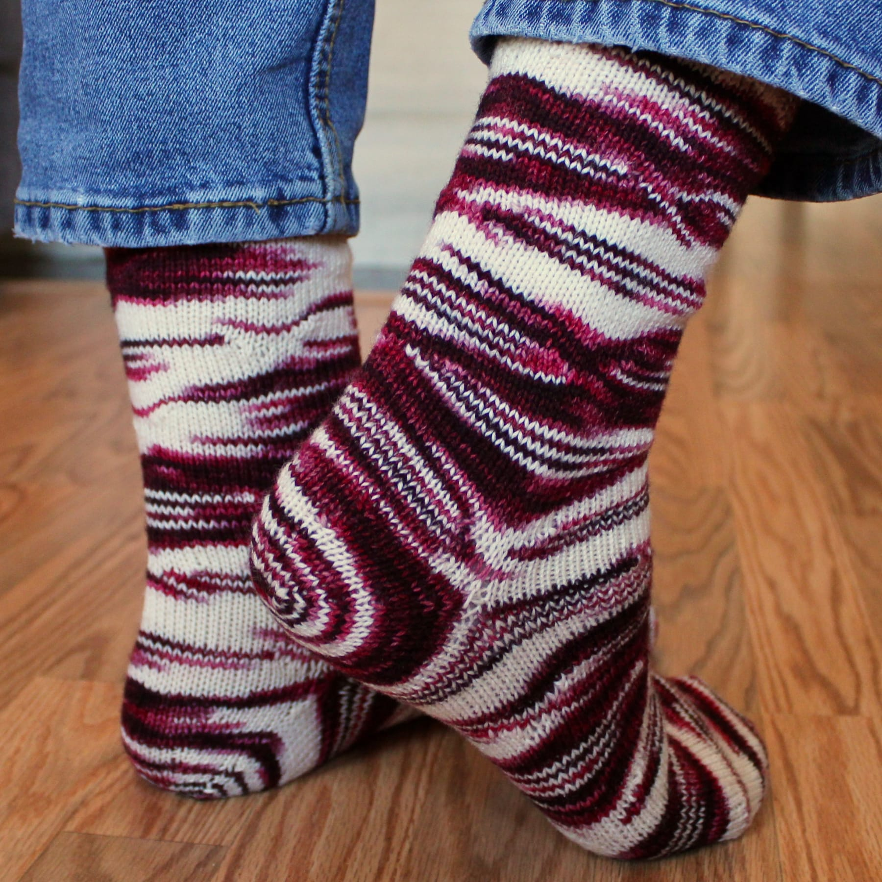 Side and back view of feet wearing red and white socks with distorted, oval-shaped pooling patterns.