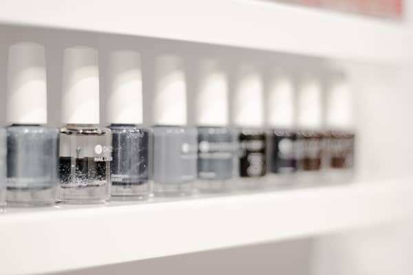 a small shelf with dazzle dry brand nail polishes