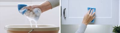 Hand squeezing soapy sponge above bucket and hand wiping cabinet with sponge