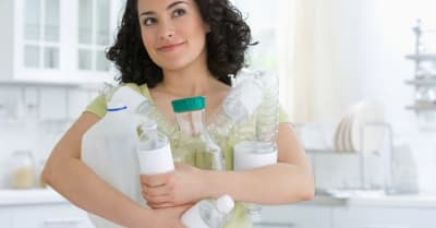 Woman holding many plastic containers in her arms