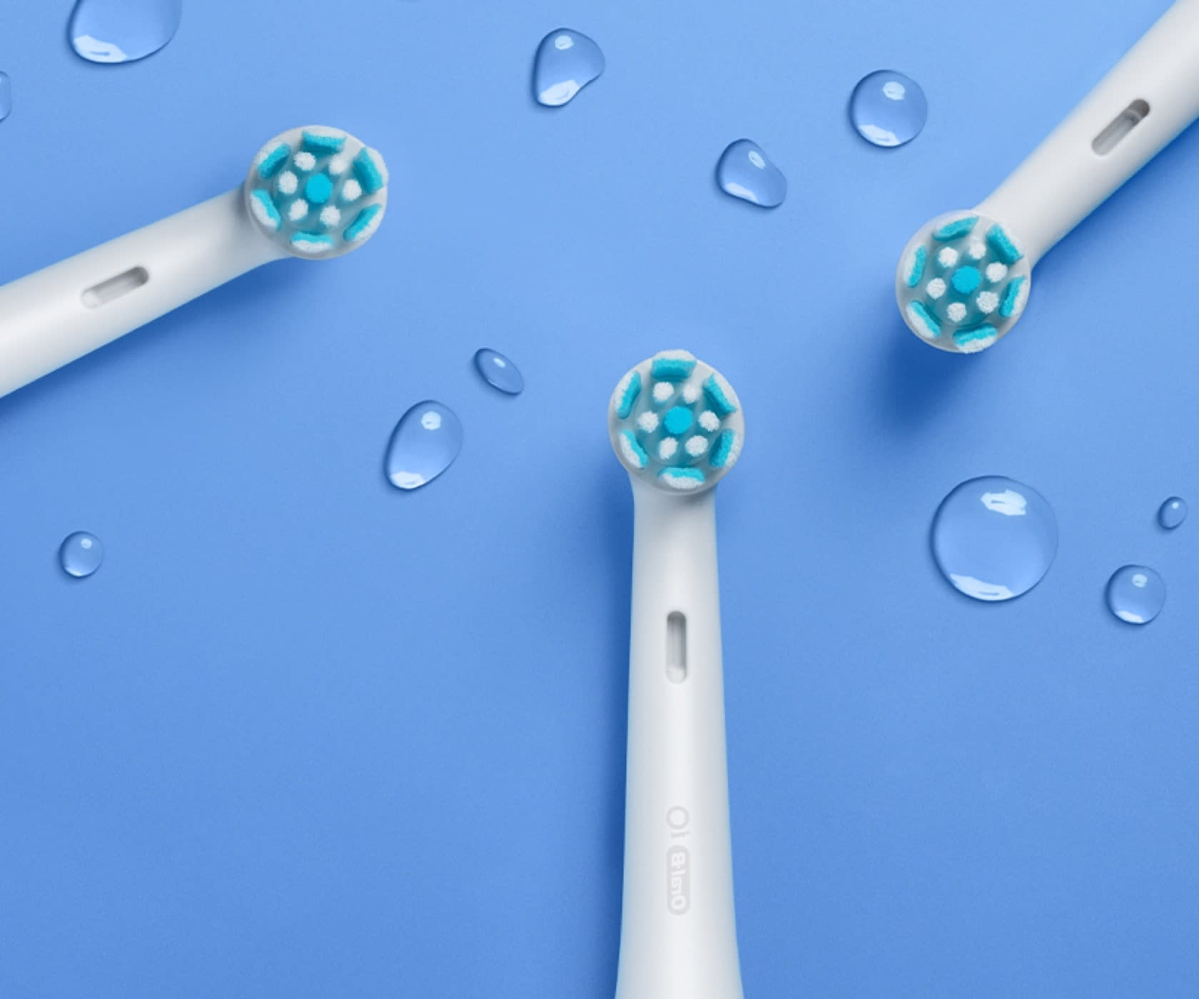 Group of white Oral-B iO Gentle Care replacement brush heads on blue surface