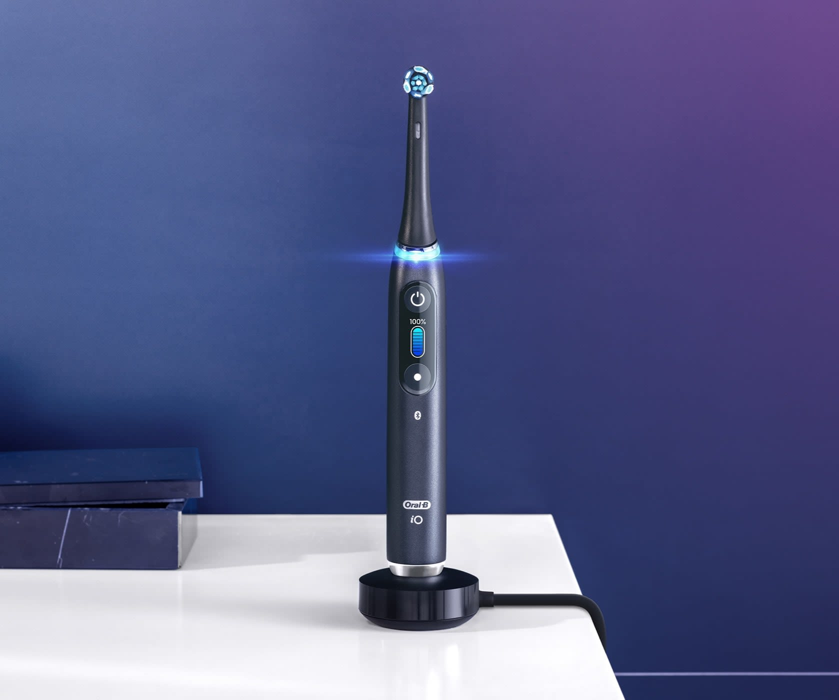 Black Oral-B iO9 electric toothbrush on magnetic charger