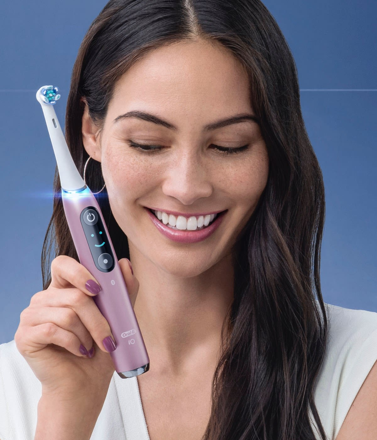 Happy Female Holding Orchid Purple Oral-B iO Electric Toothbrush