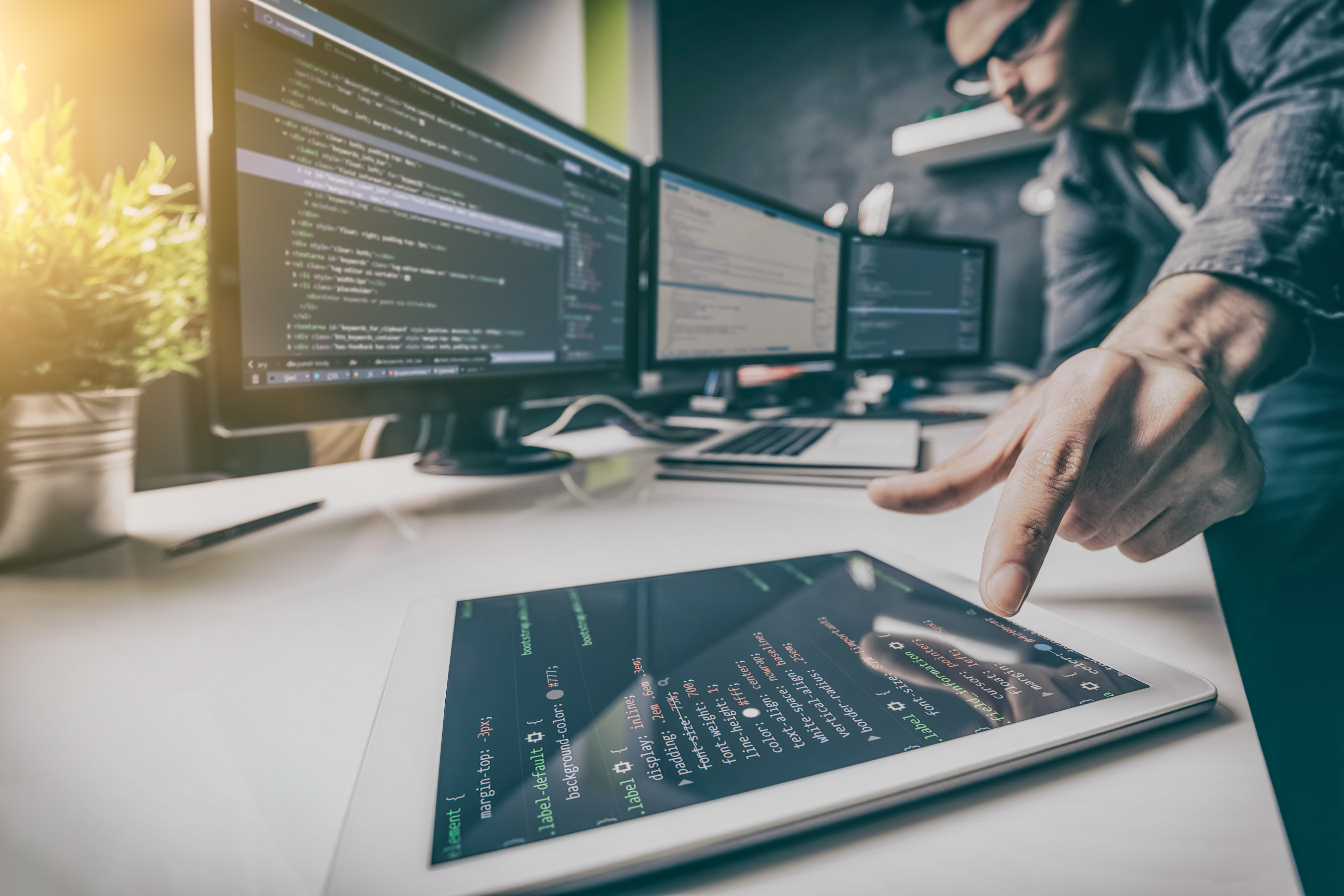 Person looking at code on multiple devices.