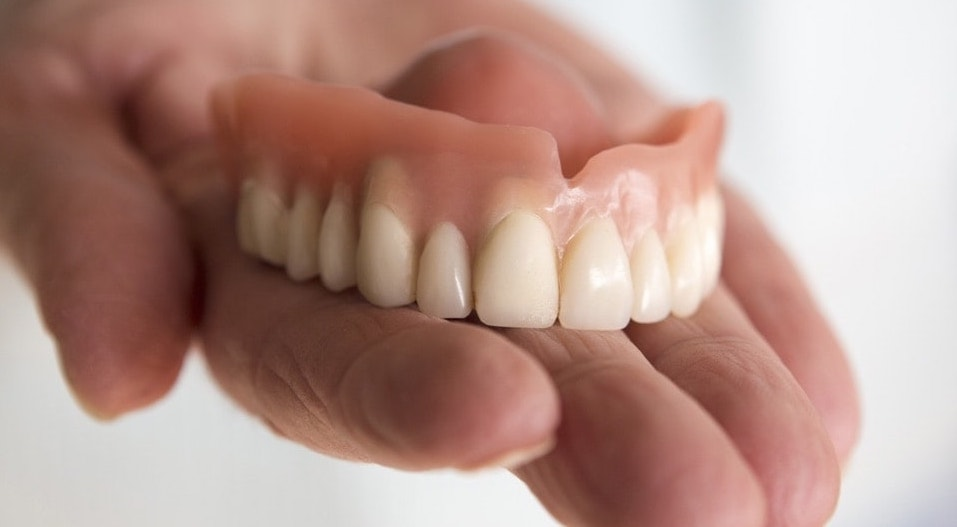 A denture on the palm of a hand