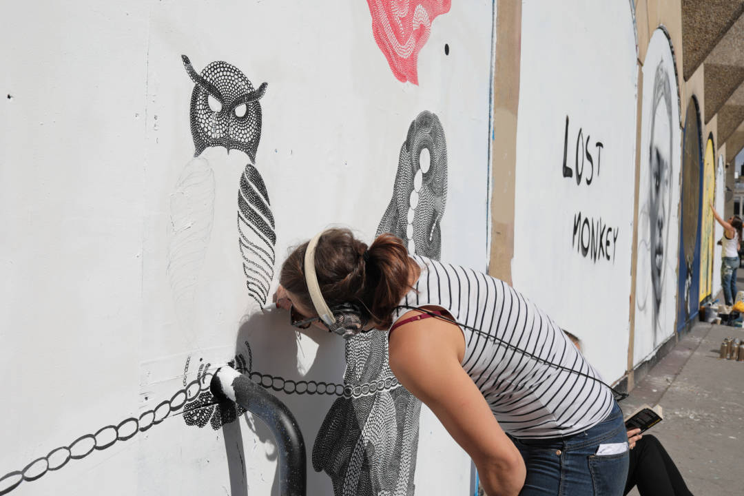 Photo of an artist carefully drawing on a wall