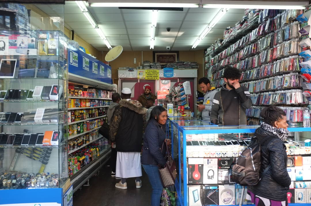 Photo of some people in a shop looking at mobile phone cases