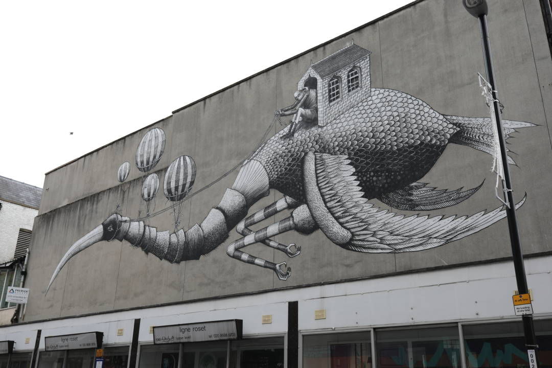 Photo of a giant painting on a building of a man in a shed riding a giant bird
