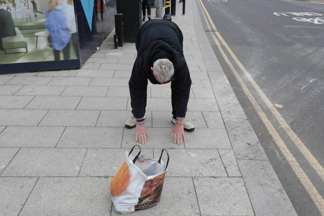 Photo of a man touching the floor on a street