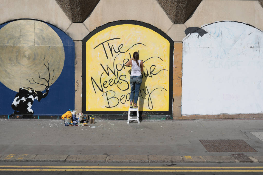 Photo of an artist writing a mural