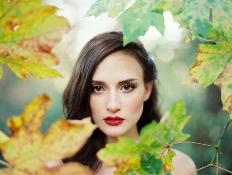 Film photograph of a woman peering through Fall leaves by Erich McVey fine art film wedding and editorial photographer.