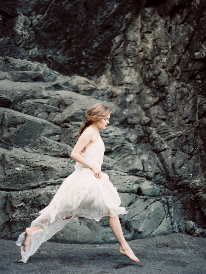 Woman running by rocks.