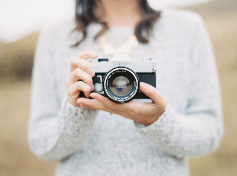 A Woman's Hands Holding A Camera