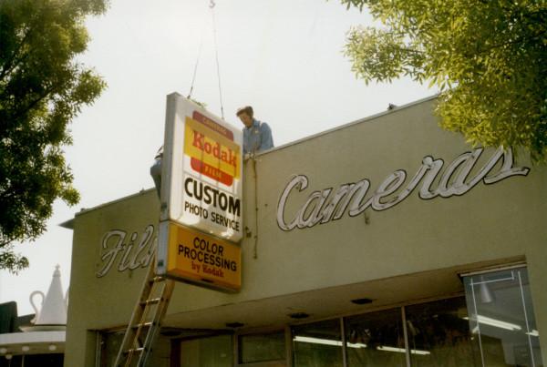 Raising the original Custom Photo Service sign.