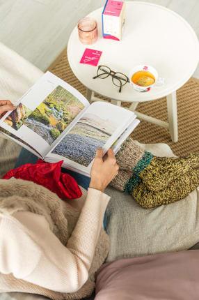 Frau liest Buch auf Sofa