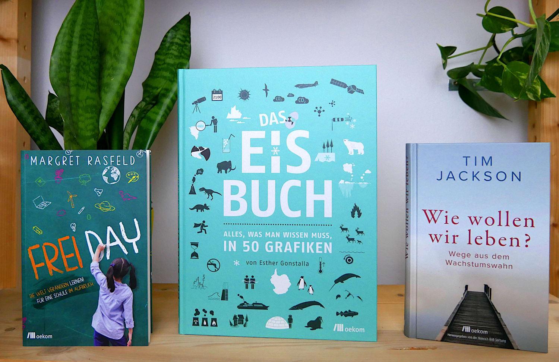 Die Bücher »Frei Day«, »Das Eisbuch« und »Wie wollen wir leben?« in einem Regal mit grünen Pflanzen