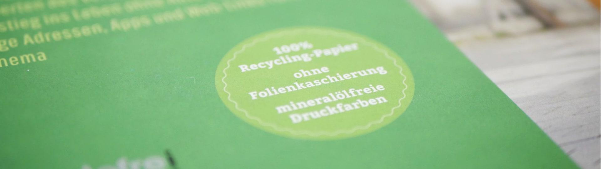 Stempel auf Buch mit Aufschrift »100% Recycling-Papier, ohne Folienkaschierung, mineralölfreie Druckfarben«