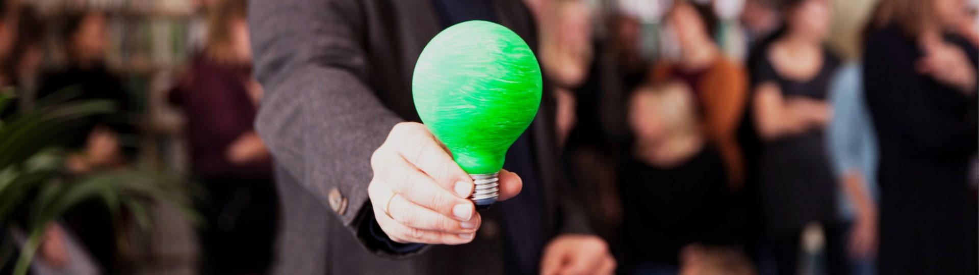 Eine Hand hält eine grüne Glühbirne – Darstellung der grünen Unternehmensphilosophie