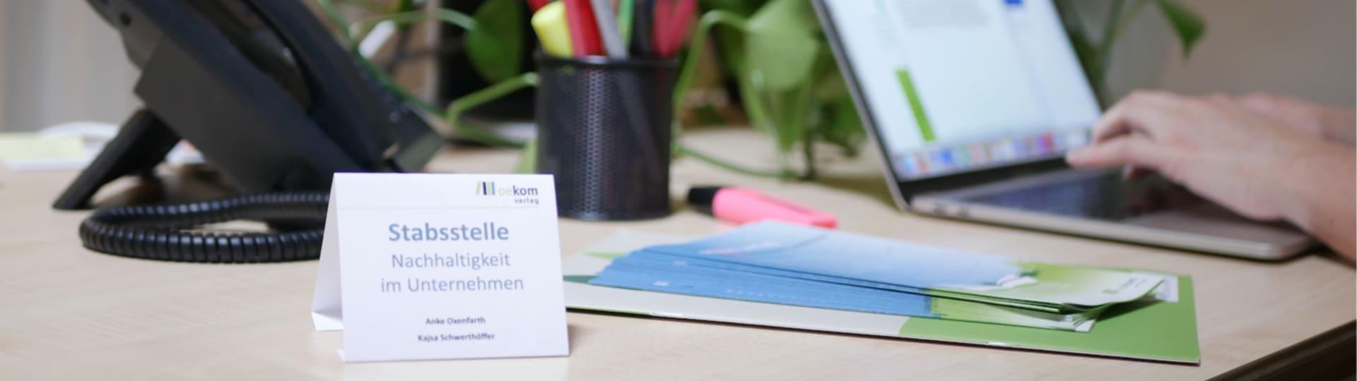 Arbeitsplatz mit Schild »Stabstelle Nachhaltigkeit im Unternehmen«