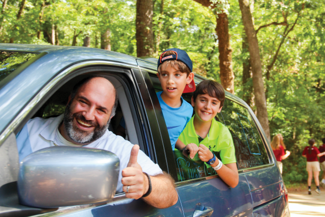 Dad gives a thumbs up as he and his two boys drive into family camp.