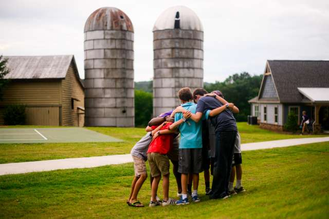 A group of boys pray in front of the silos at Chimney Point.