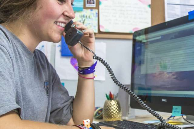 Administrative Assistant answers phone at desk