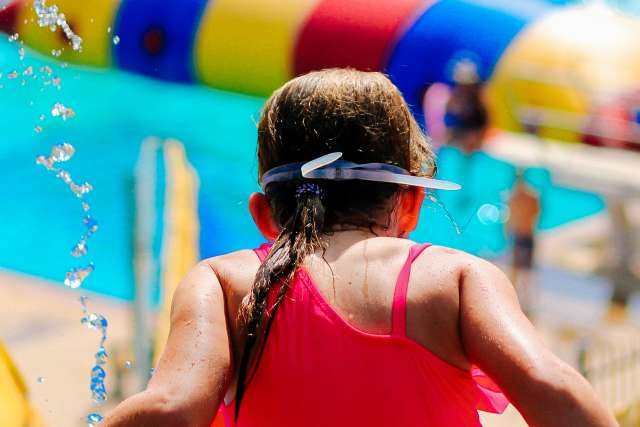Girl prepares to go down a water slide at family camp