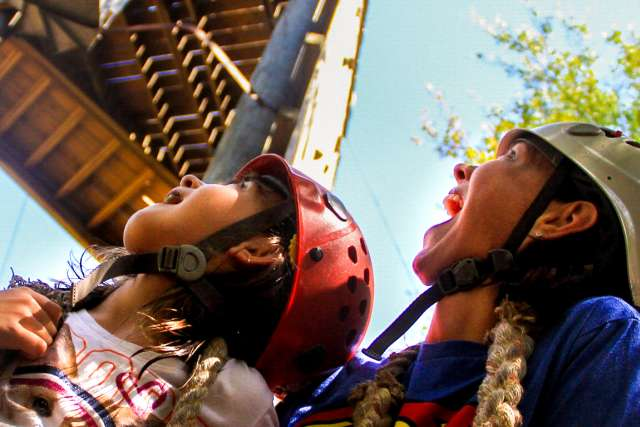 Girl and Mom look up at zipline tower