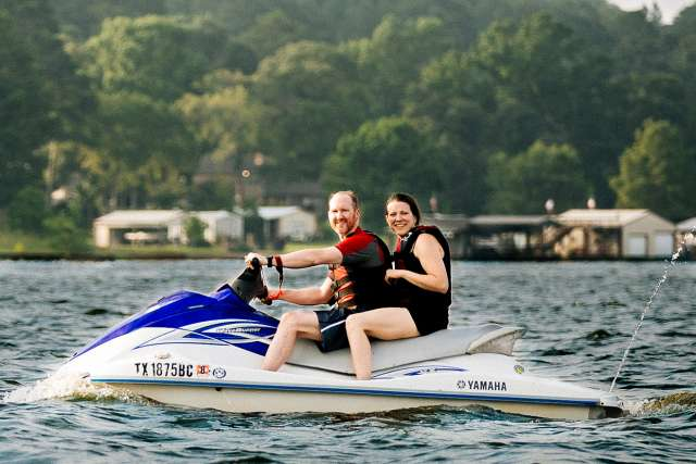 Husband and wife ride a wave runner across the lake